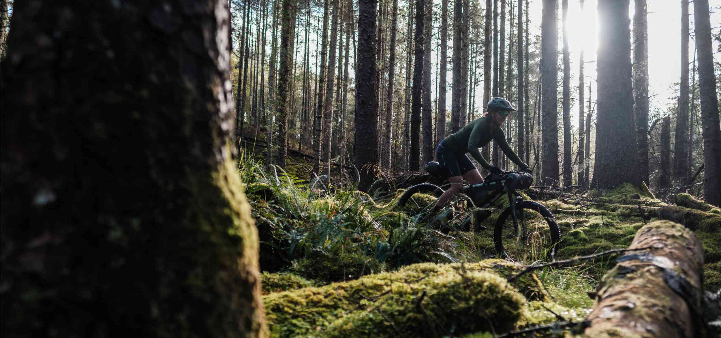 Jenny Tough riding a backcountry trail on her mountain bike with Backcountry Series bikepacking bags