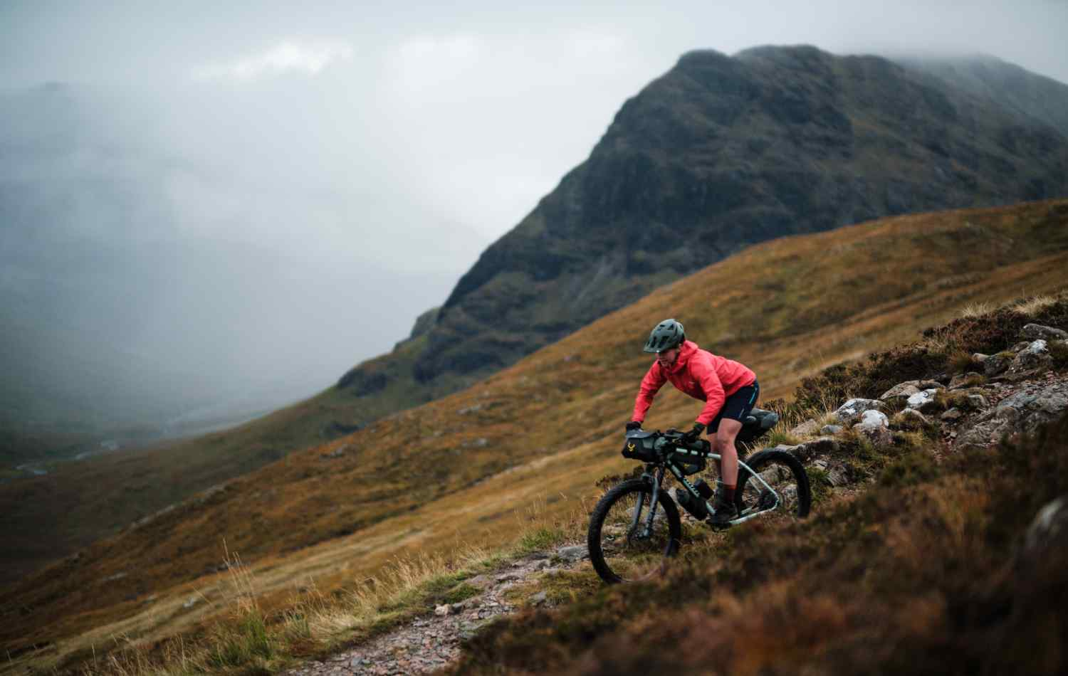 Jenny Tough riding off road with her mountain bike covered in Backcountry Series bikepacking bags