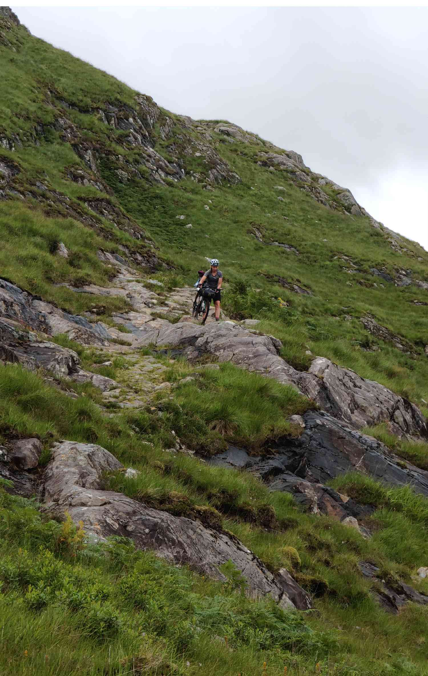 A lost cyclist hikes down a mountainside with her bike