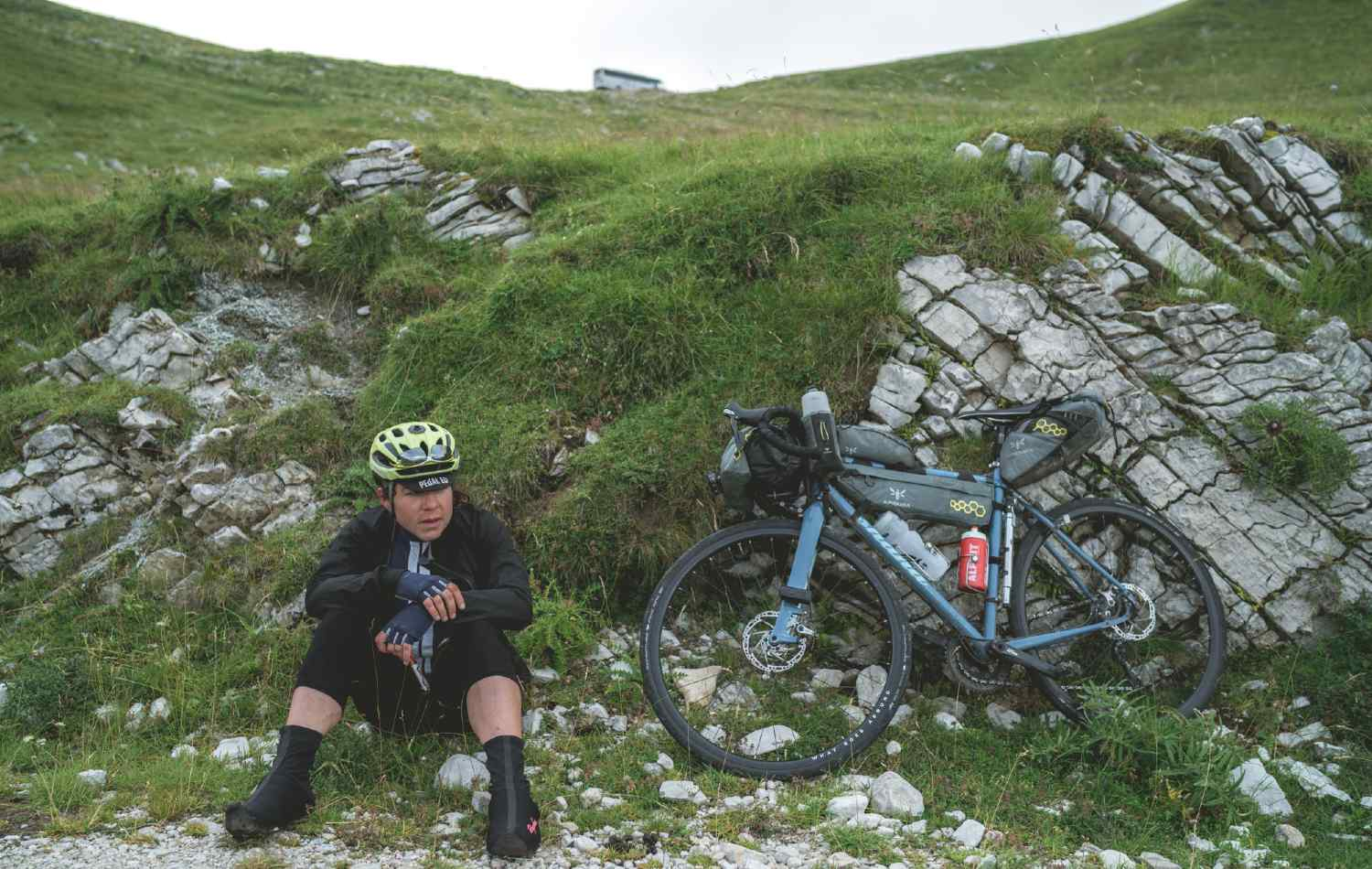 A cyclist pauses by the side of the road to take stock
