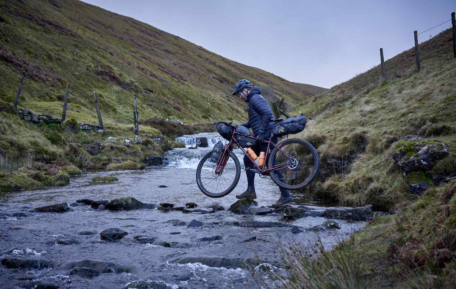 Marcus crosses a river, carrying his bike