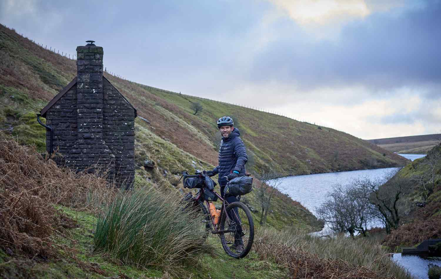 Marcus stands with his bike by a bothy next to the river he camped by