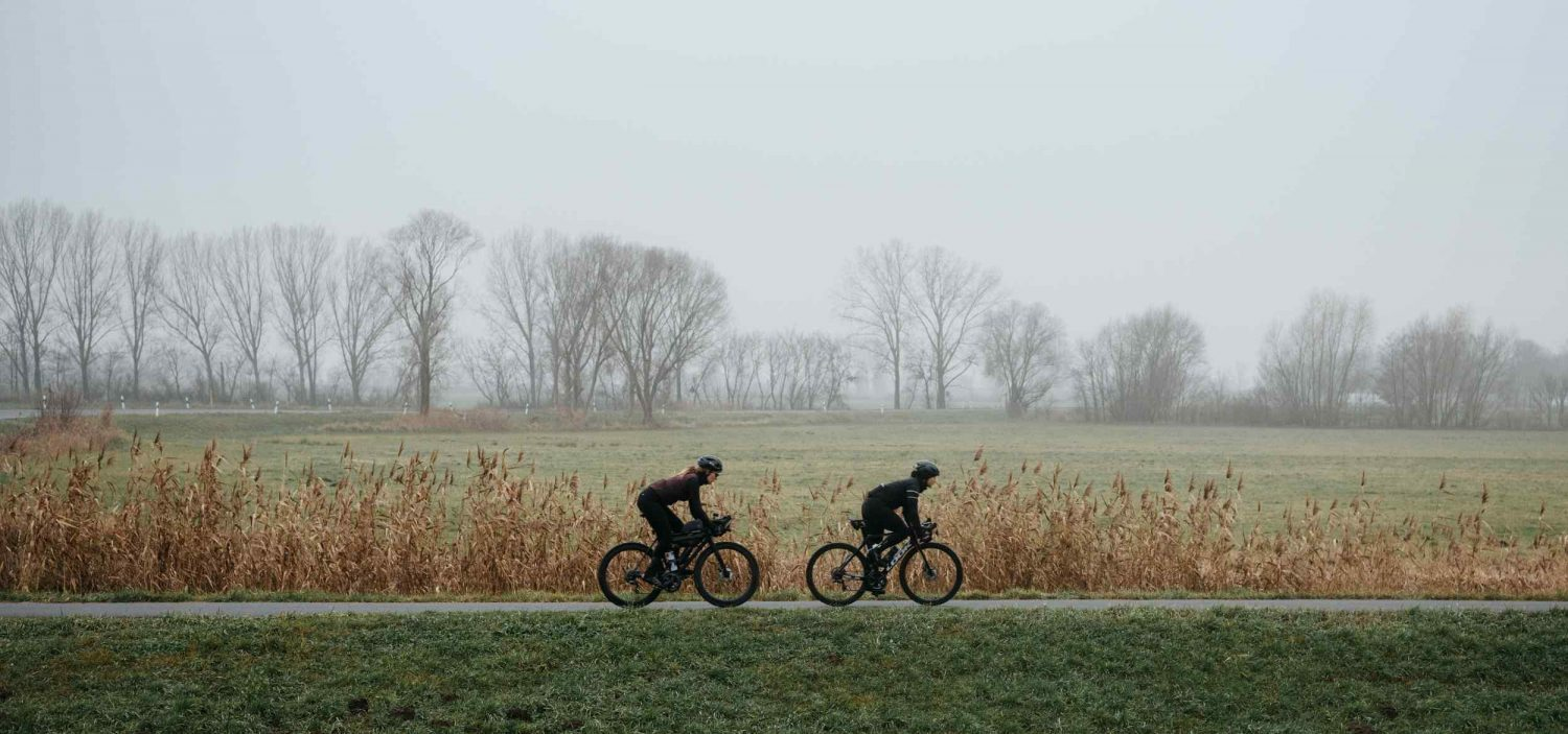 Two cyclists ride along a misty road