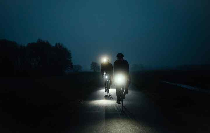 Two riders at night, brightly lit
