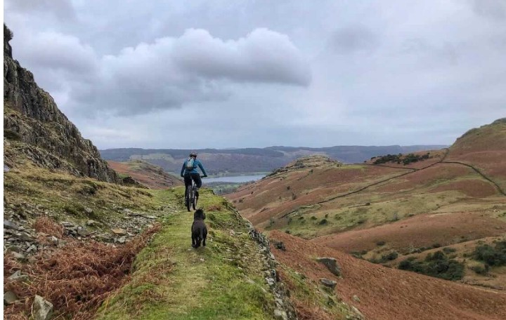 Alice riding her mountain bike in the Lake District with her trail dog