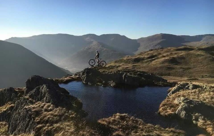Alice on top of a summit on her mountain bike in the Lake District