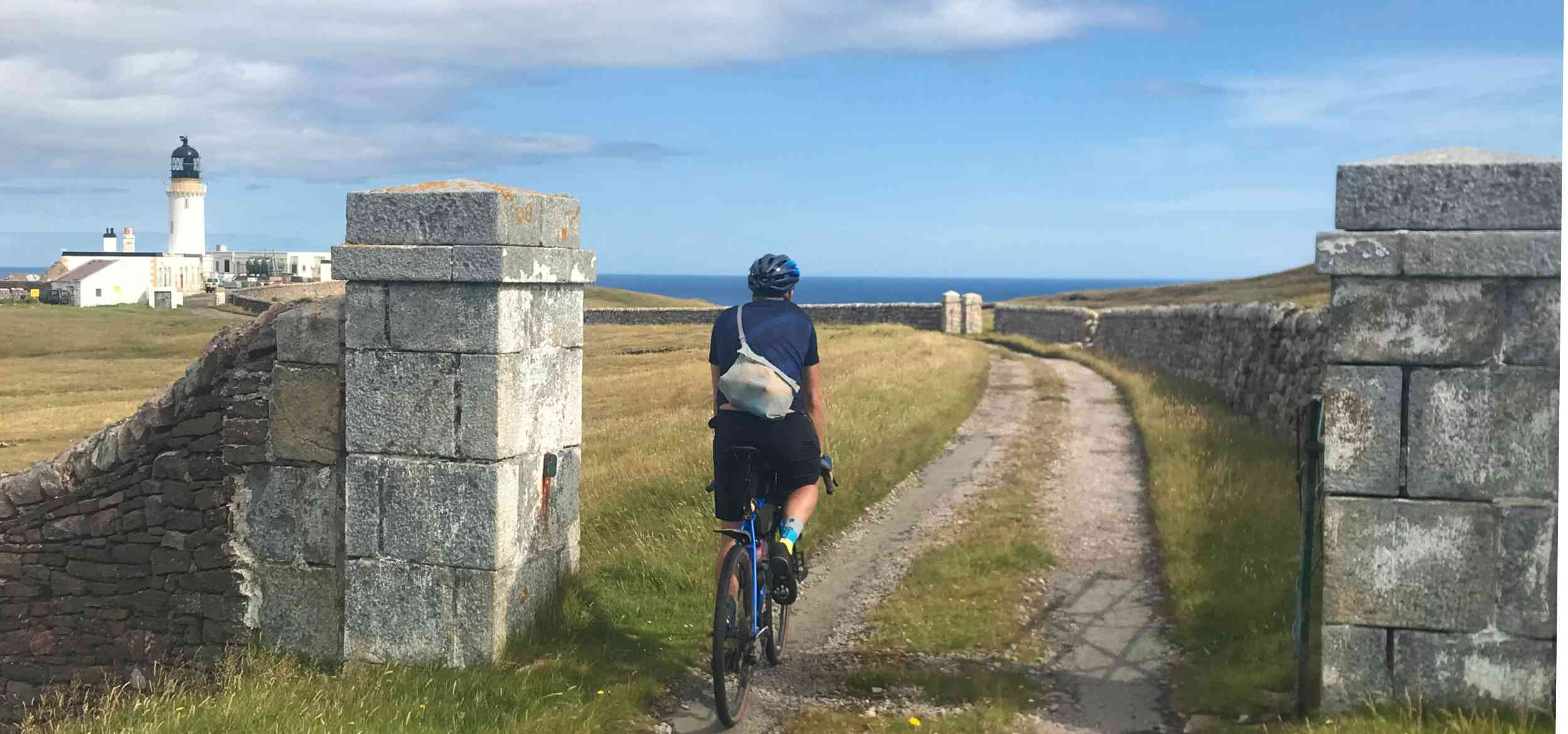 Chris riding his gravel bike to the lighthouse at Cape Wrath