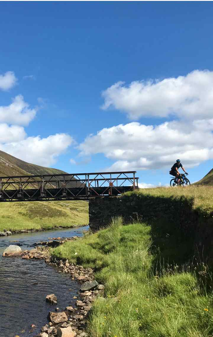 Chris riding his gravel bike on a remote gravel trail in the Scottish Highlands