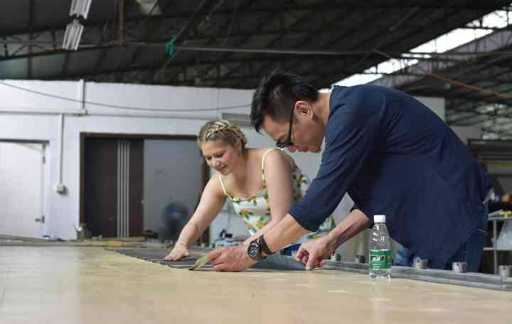 A member of the product team works with a factory technician to refine designs