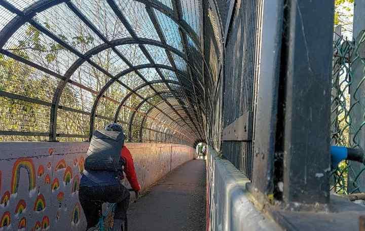 Josie cycling over a bridge