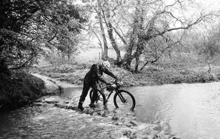 Ali pushes his mountain bike through a river