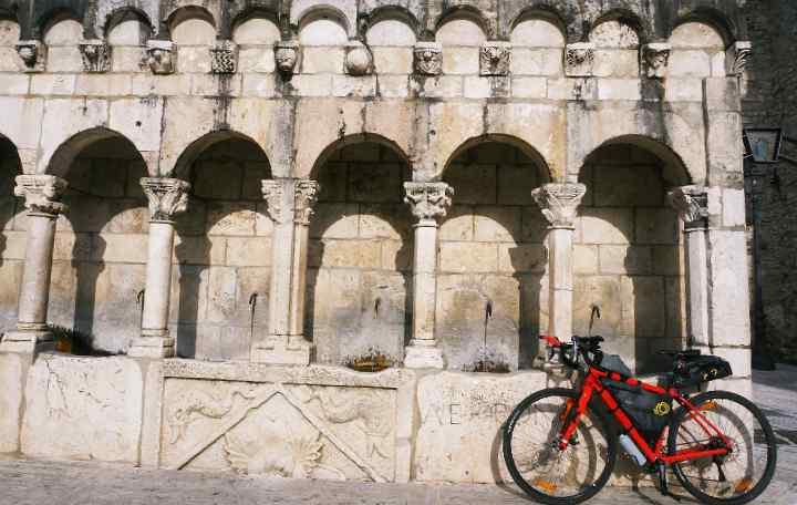 Marco's bike leans against an ancient fountain