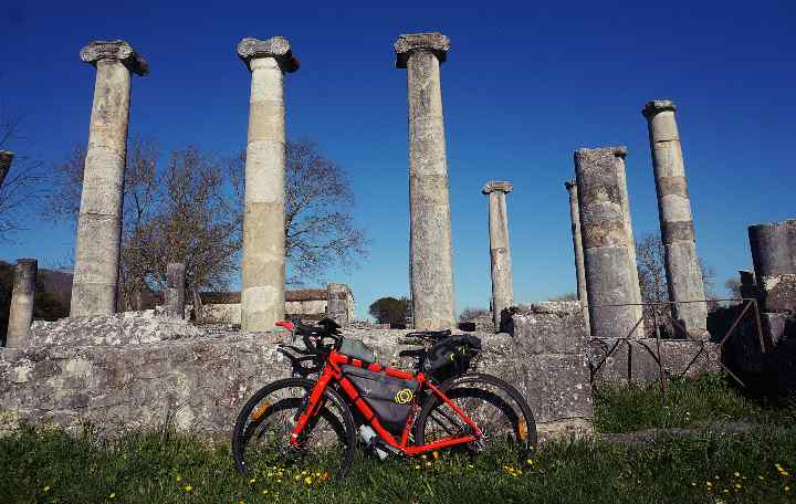 Mario's bike leans against ancient ruins with columns pointing toward the sky