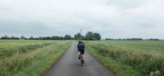 Ali rides along a straight road in the fens