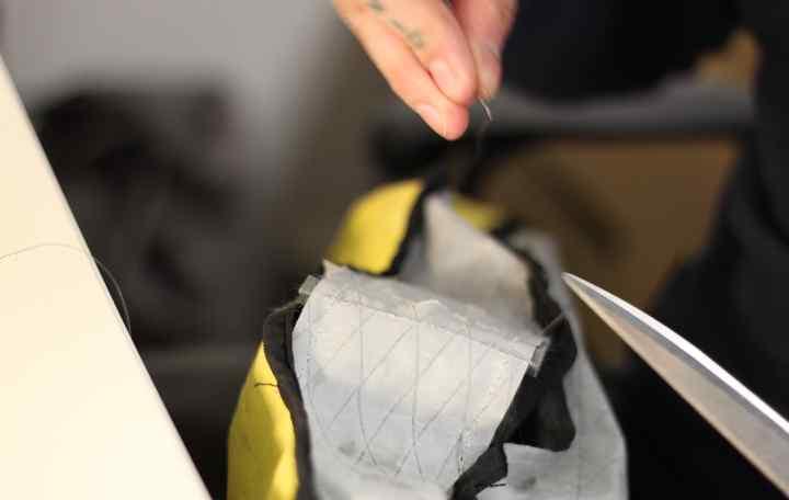 An Apidura repair technician tidies up a seam