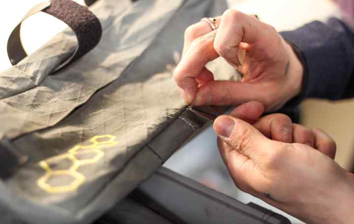 An Apidura repair technician repairs the damage to Patrick's Frame Pack