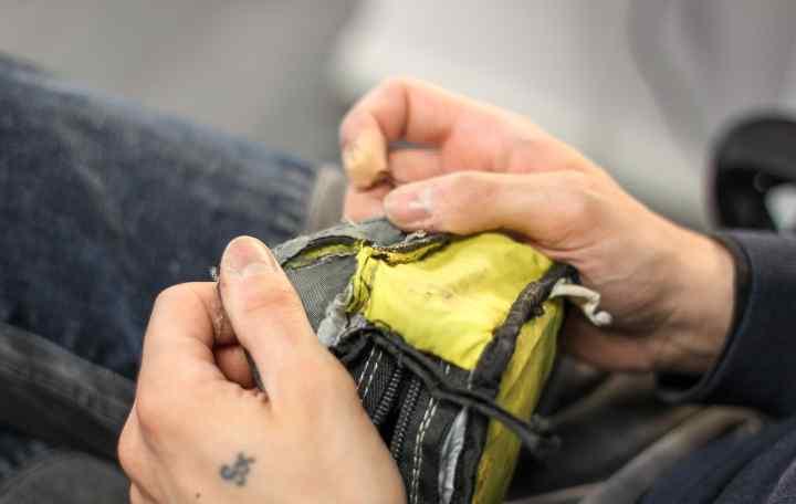An Apidura repair technician unpicks stitches on a pack