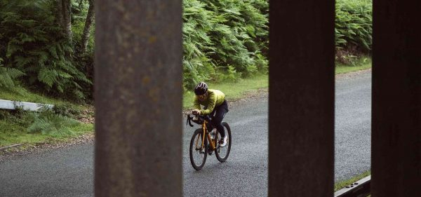 A rider racing under a bridge, with the Racing Aerobar Pack attached to their bike