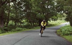 A cyclist races along a forest road with the Racing Aerobar Pack attached to their bike