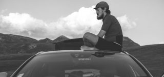 Mike Hall sits on top of a control car in the mountains