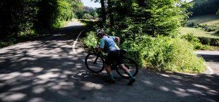 Maren walks her bike up a steep hairpin on a wooded climb
