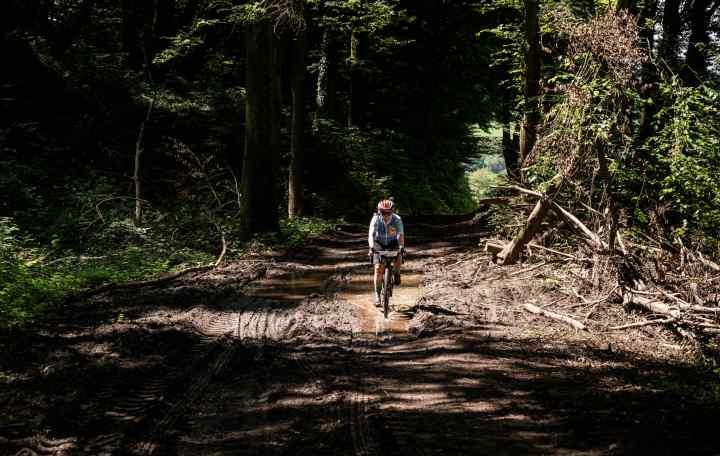 Maren rides down a muddy forest trail