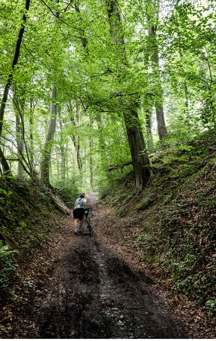 Maren pushes her bike up a steep path in the woods