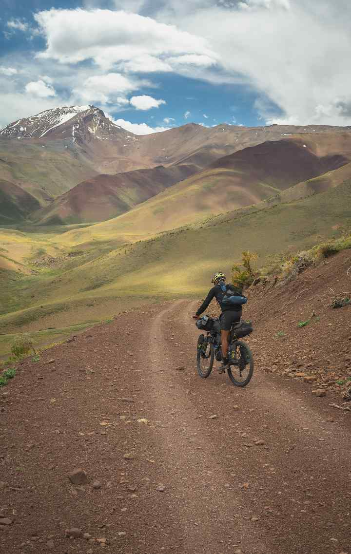Gonzalo rides along a mountain gravel road against a backdrop of snow covered mountains