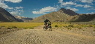 Gonzalo rides down a dirt road in front of the mountains, smiling at the camera