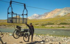 Gonzalo stands next to his bike, strapped to a cage on a zipwire for crossing the river
