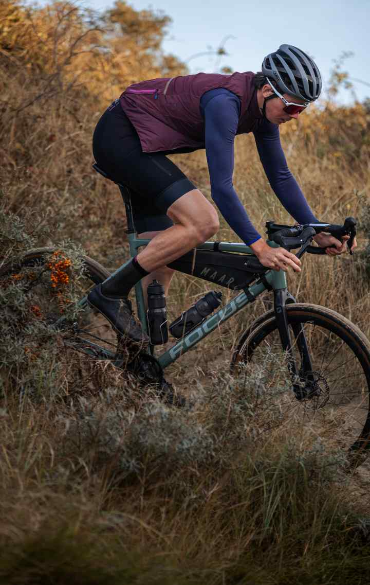 A rider descends on a dusty hillside, wearing MAAP's new Alt_Road range, with a MAAP x Apidura Frame Pack on their bike