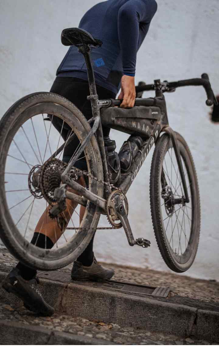 A cyclist carries their bike up a set of stairsup a