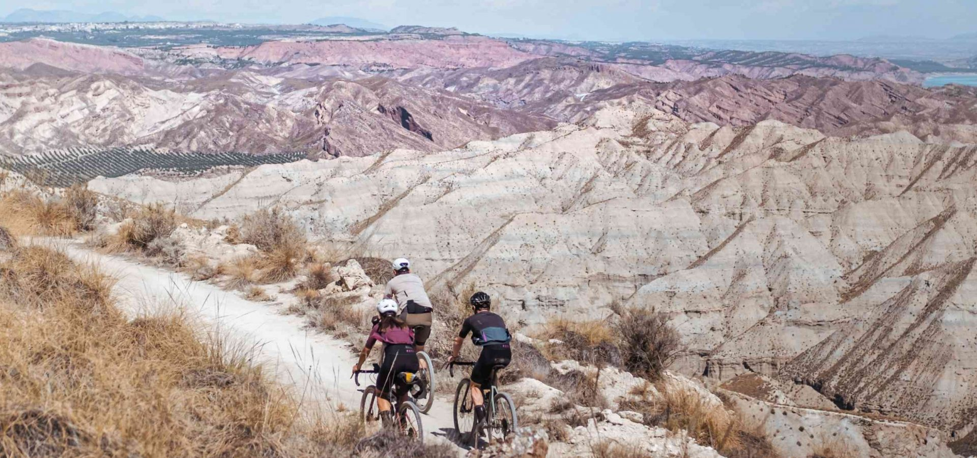 Two cyclists ride away from the camera on a gravel road in the desert, with mountains in the background