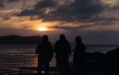 Three riders stand silhouetted against a sunset at the coast