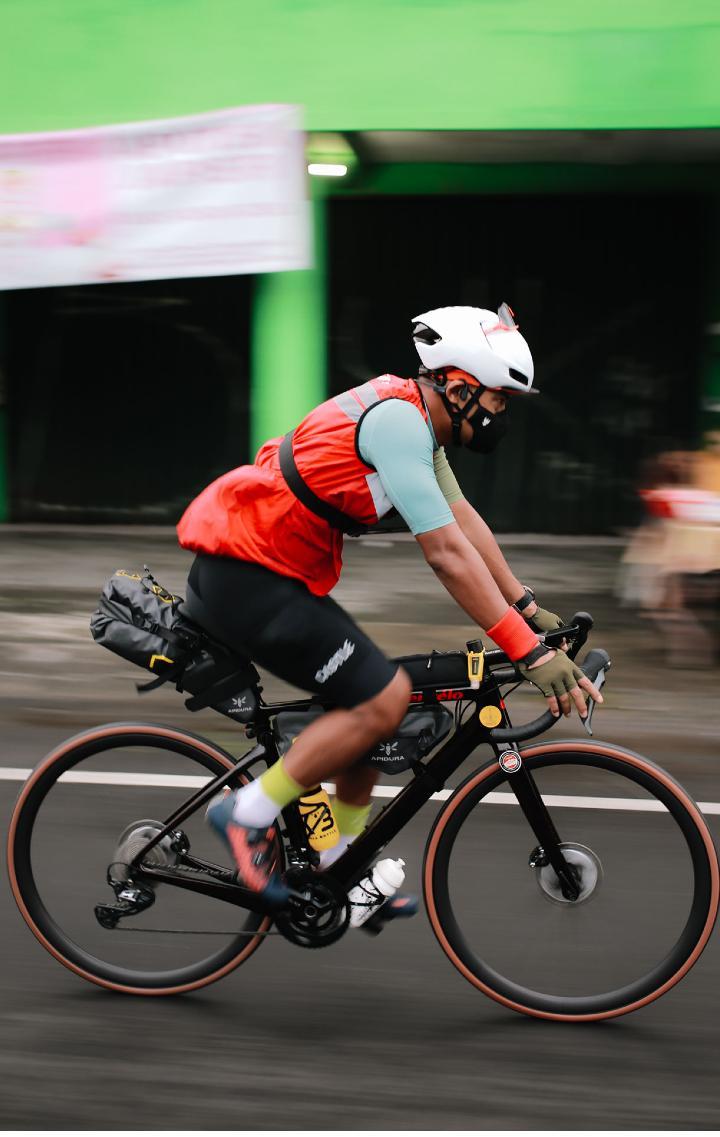 An Indonesian Randonneur viewed from the side, riding down an urban street
