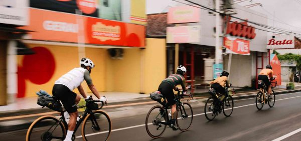 A group of four Indonesian audax riders heading away from the camera on an urban street, mid event