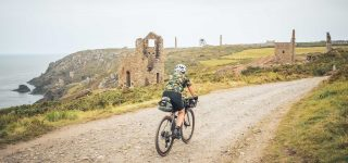 Jo rides a gravel path through an abandoned mine on the coast of Cornwall