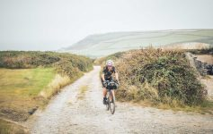 Jo rides down a gravel path with the sea and cliffs visible in the background