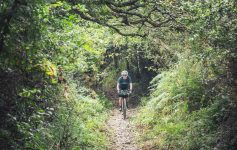 Jo rides toward the camera down a gravel track surrounded by trees and greenery