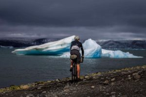 a man cycling with a repaired saddle pack on his bike toward an ice fjord